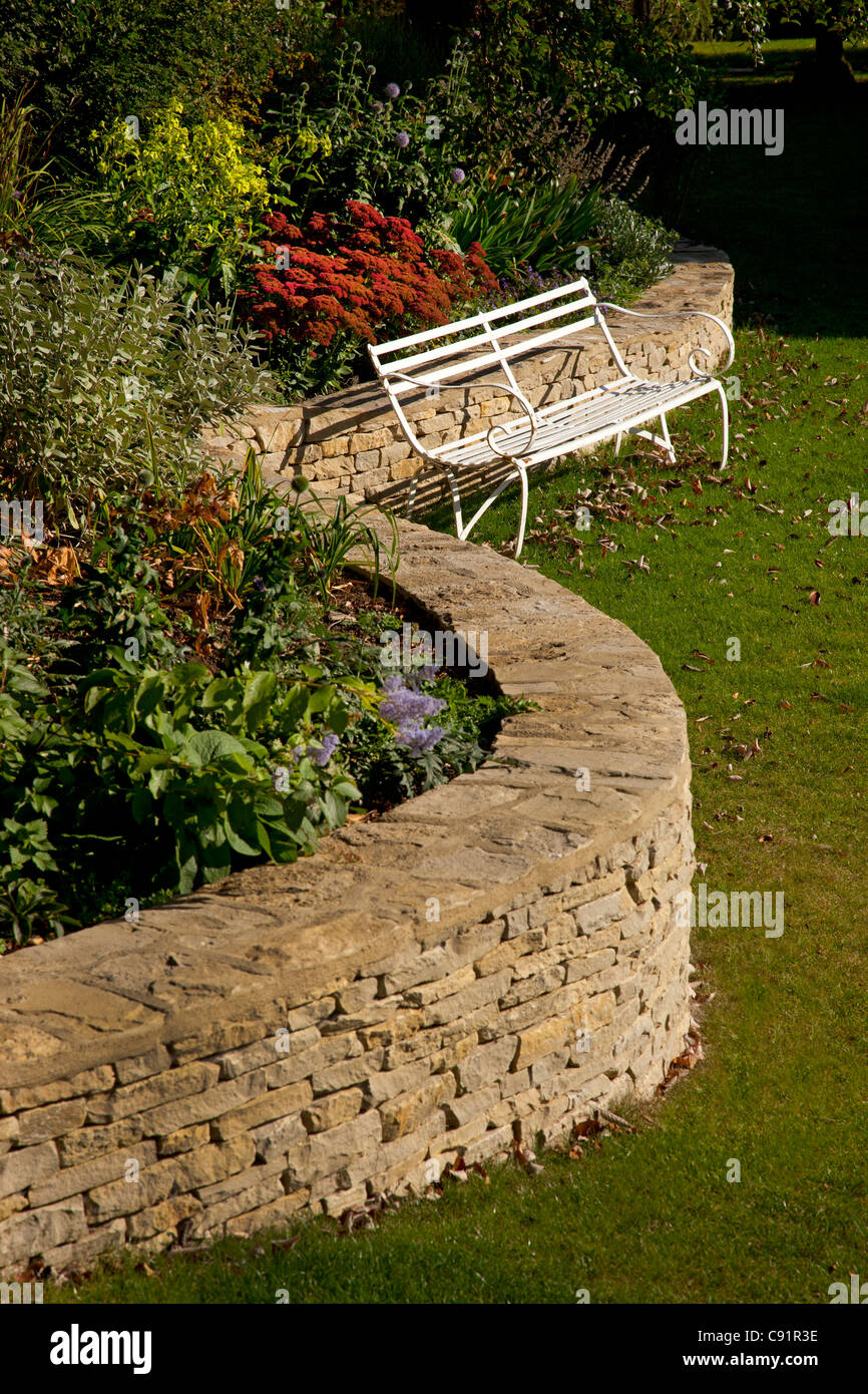 Curved cotswold stone wall with raised flower bed in English garden