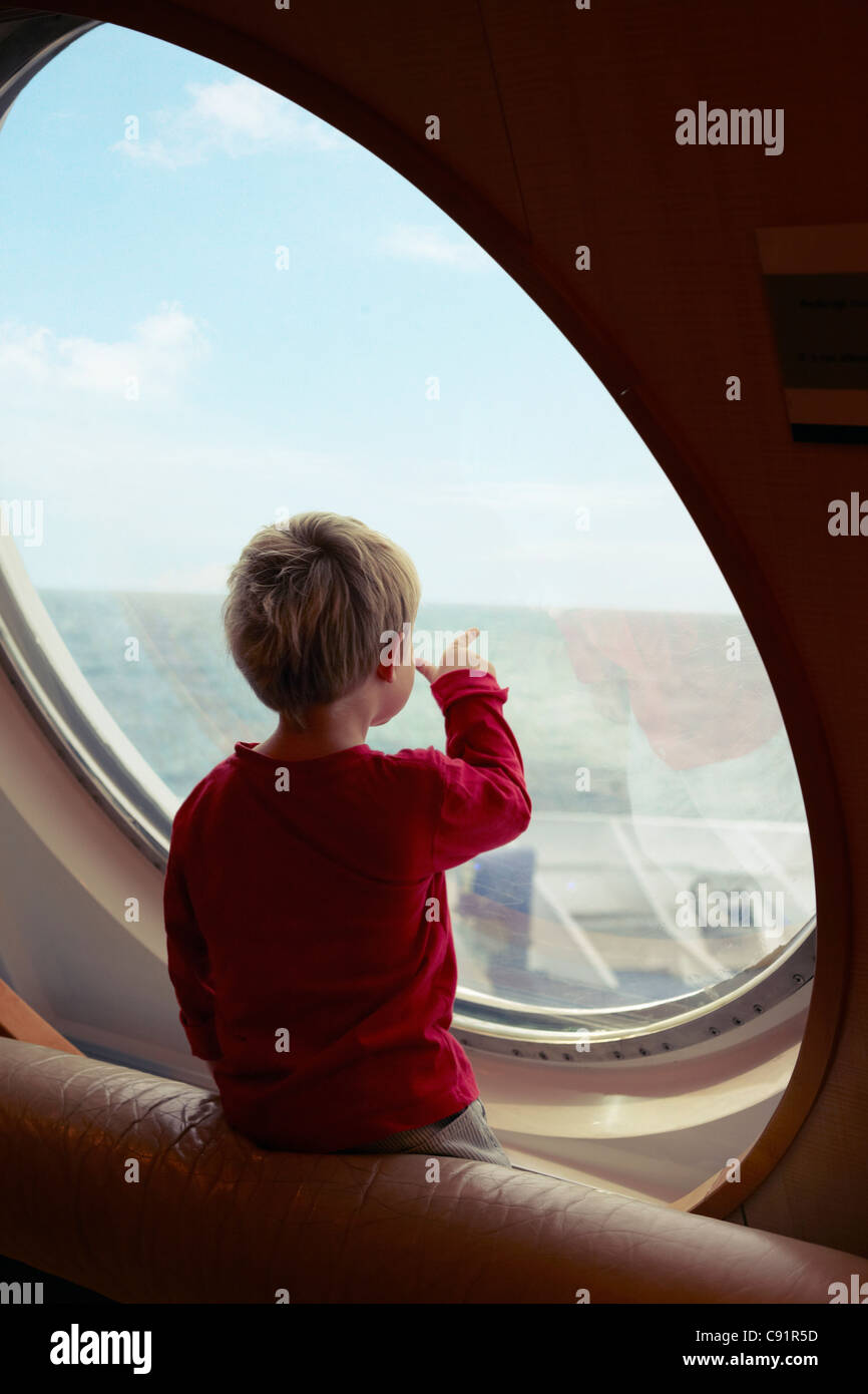 Boy admiring ocean from ship window Stock Photo