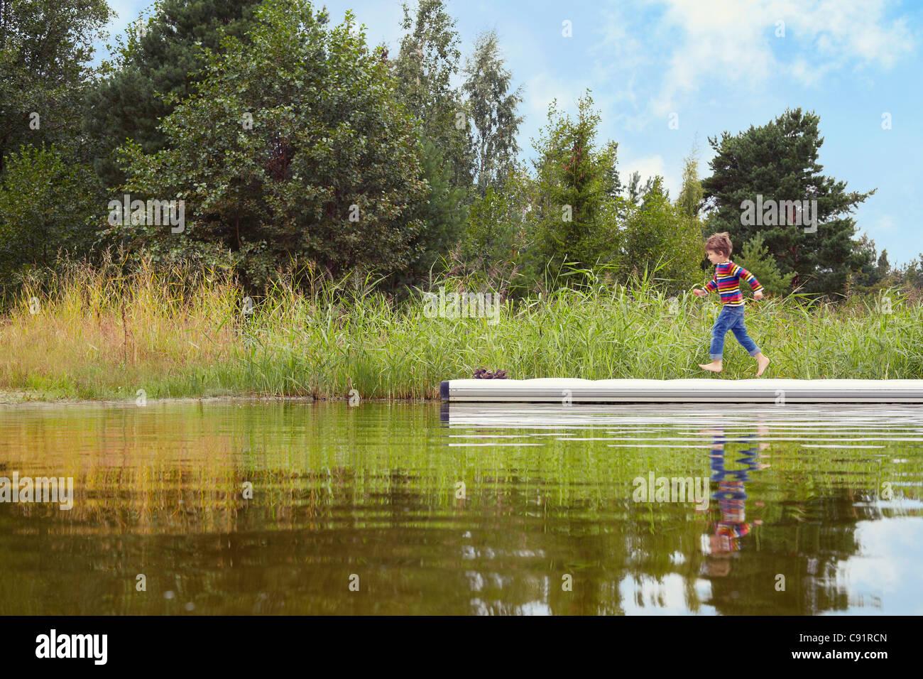 Boy running on wooden pier - Stock Image