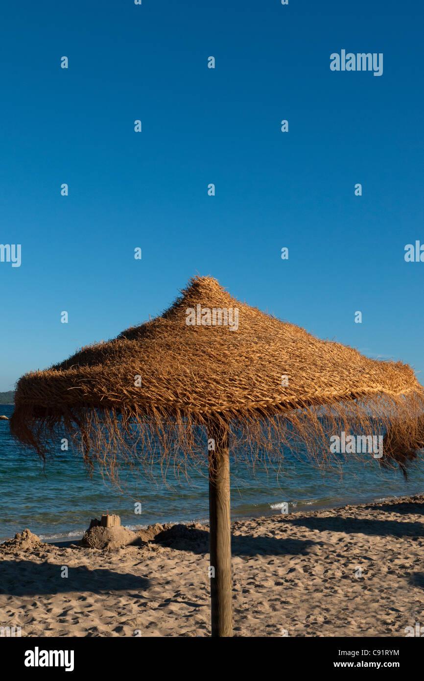 Wicker parasol on sunny summer sandy beach, Puerto de Pollenca, Mallorca, Spain - Stock Image