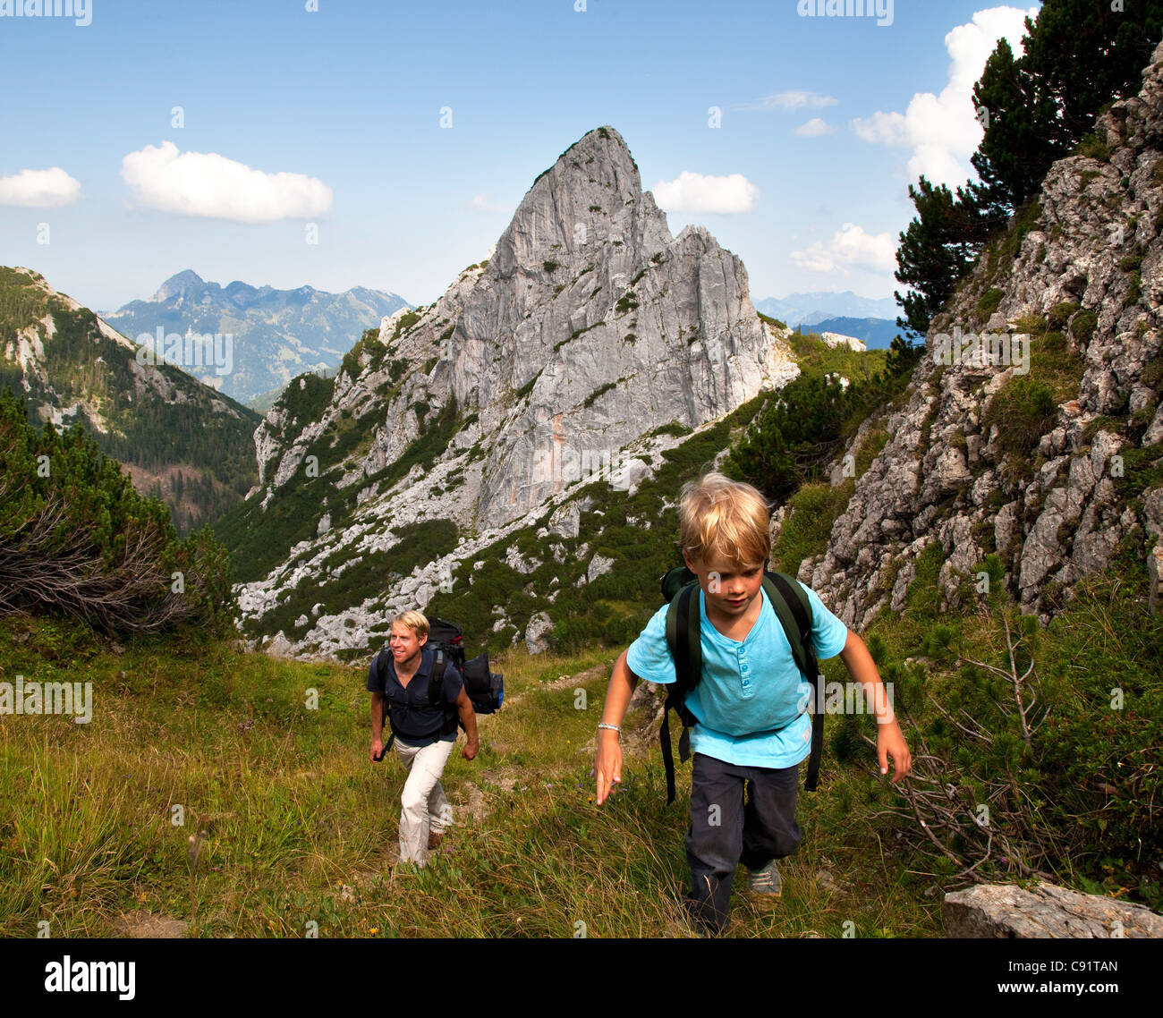 Father and son hiking on mountain path - Stock Image