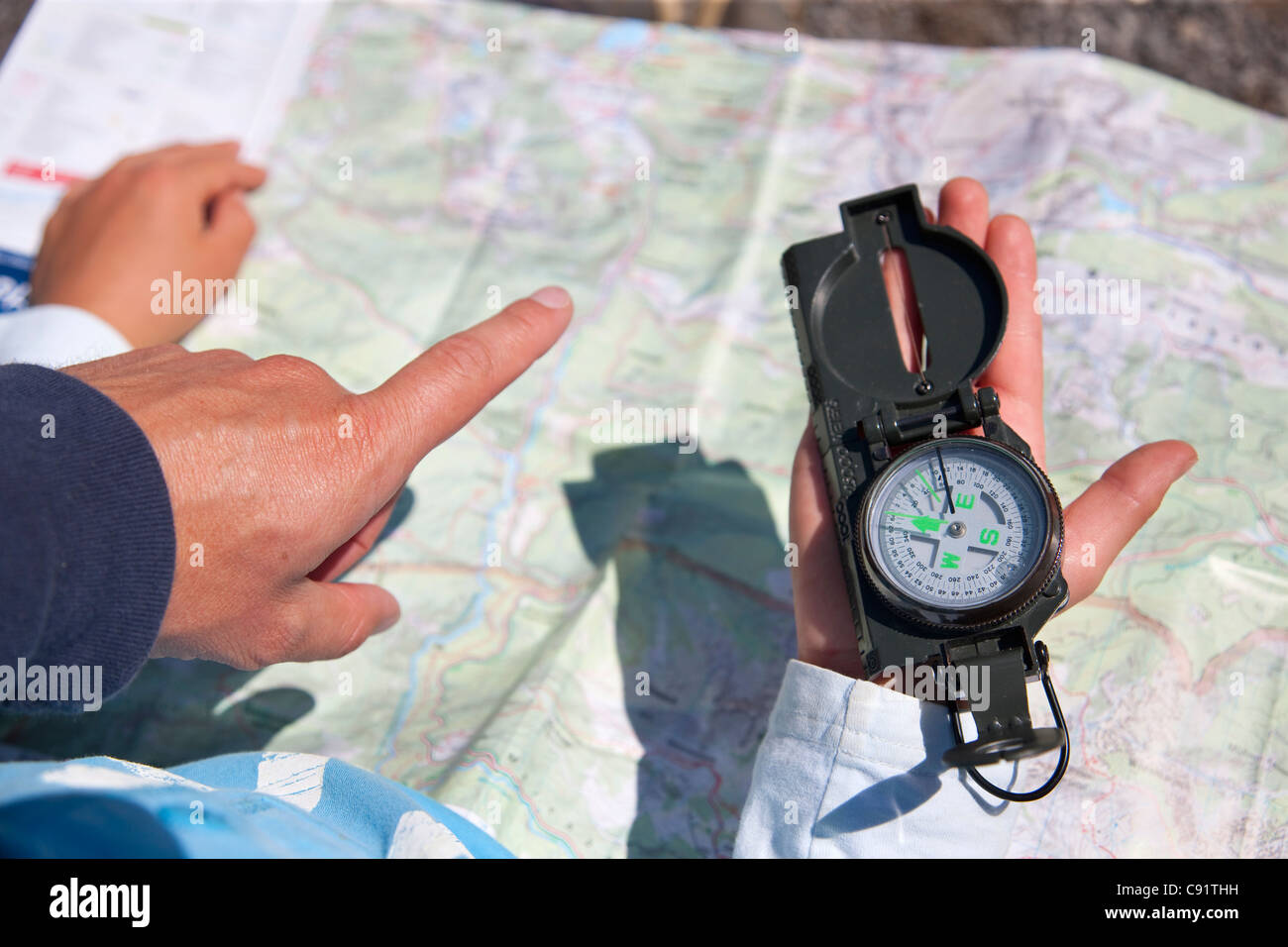 Father and son using compass and map - Stock Image