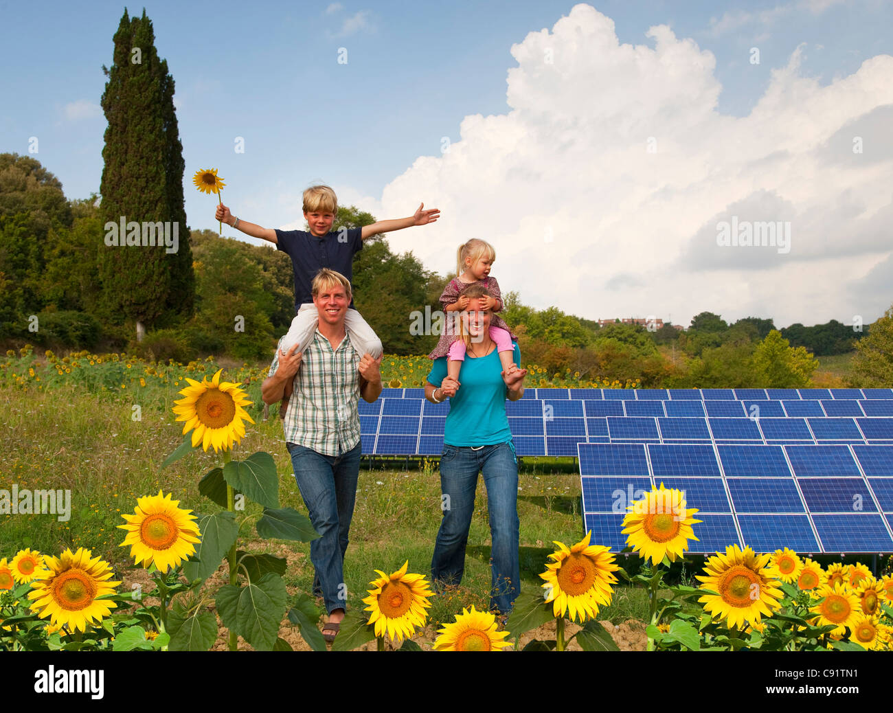 Family in field by solar panels - Stock Image