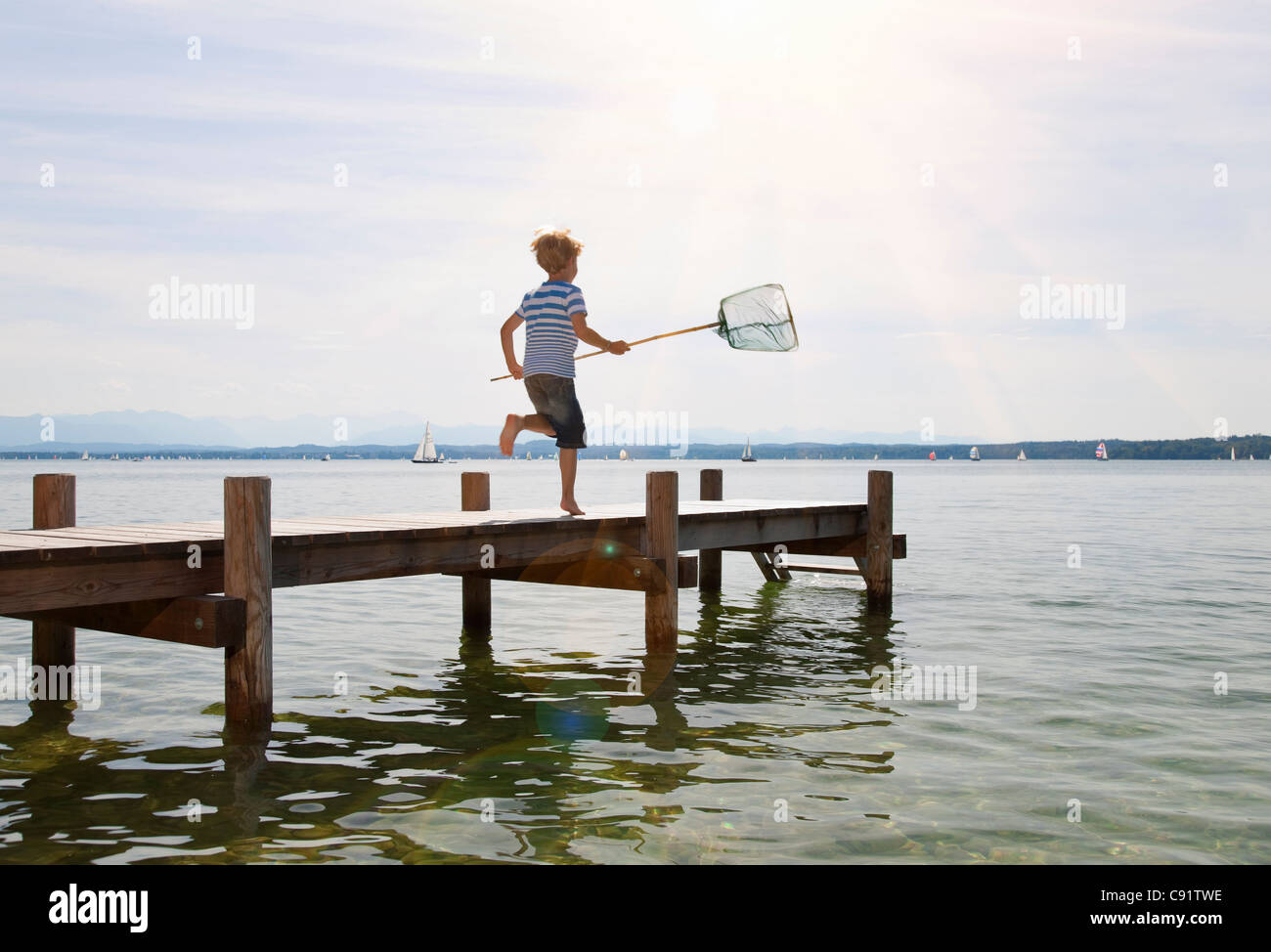 Boy running on dock with fishing net - Stock Image