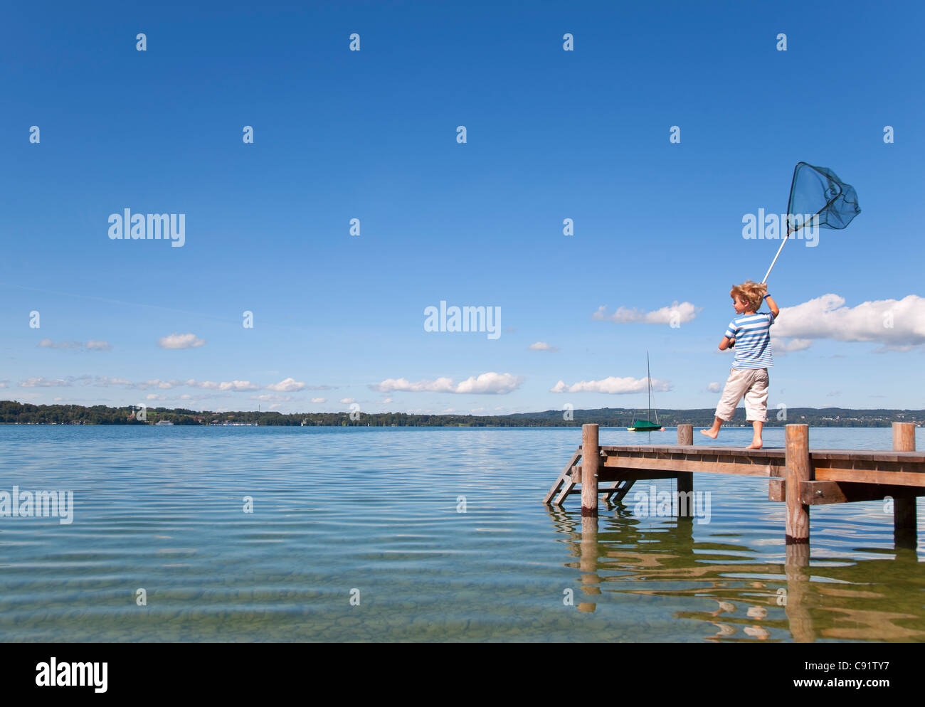 Boy fishing with net in lake Stock Photo