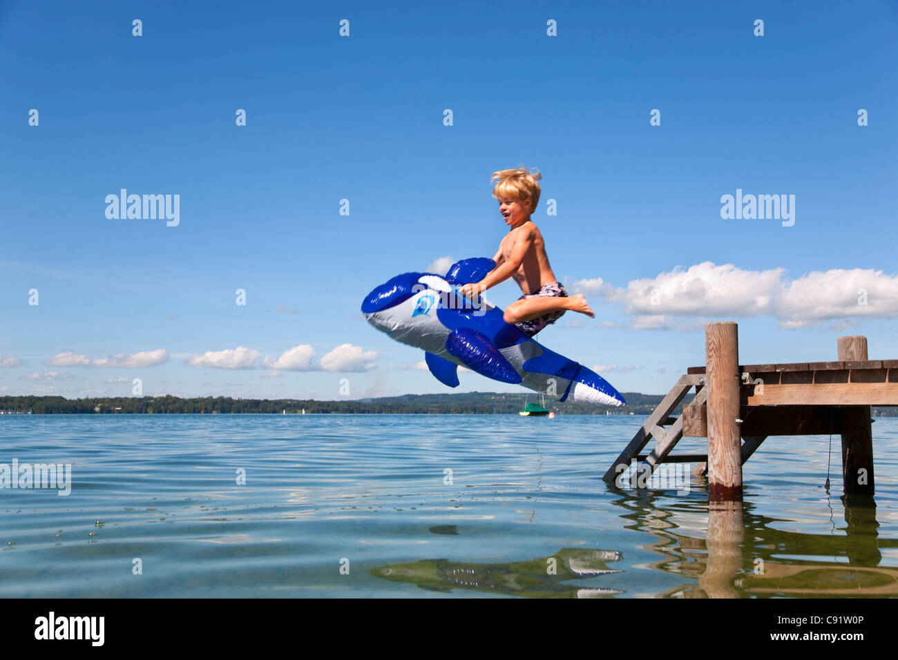 Boy jumping into lake with toy whale - Stock Image