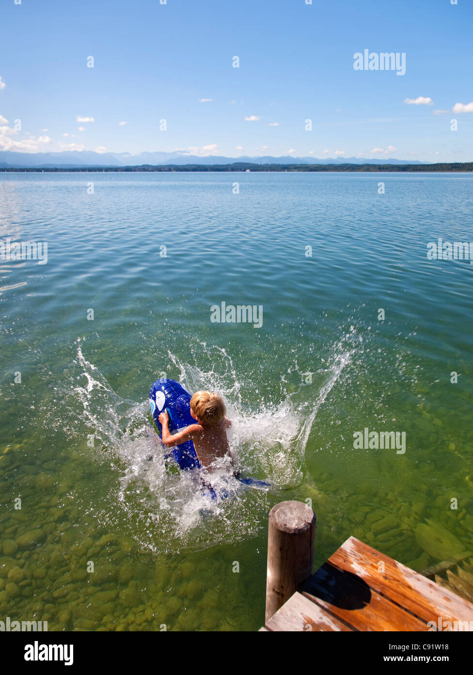 Boy floating in lake with toy whale - Stock Image