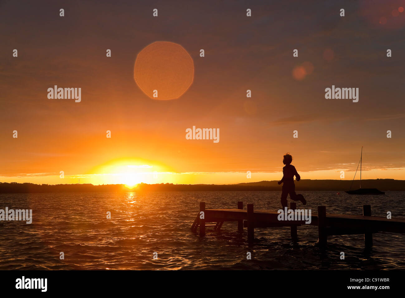 Boy running on wooden dock at sunset - Stock Image