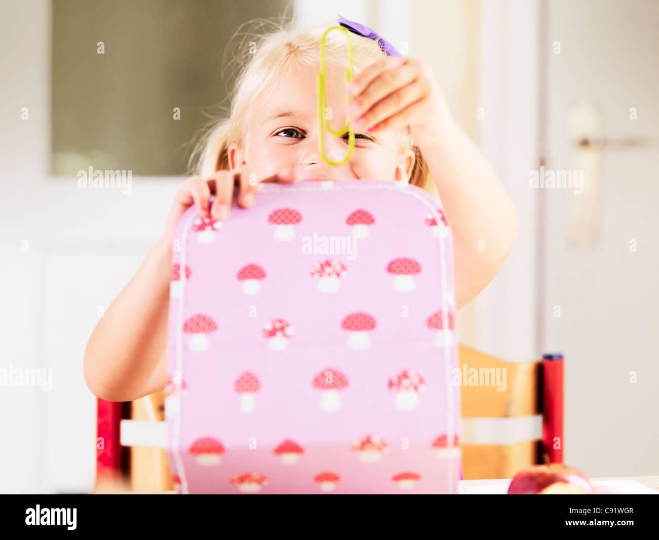 Girl holding oversize paper clip at desk - Stock Image
