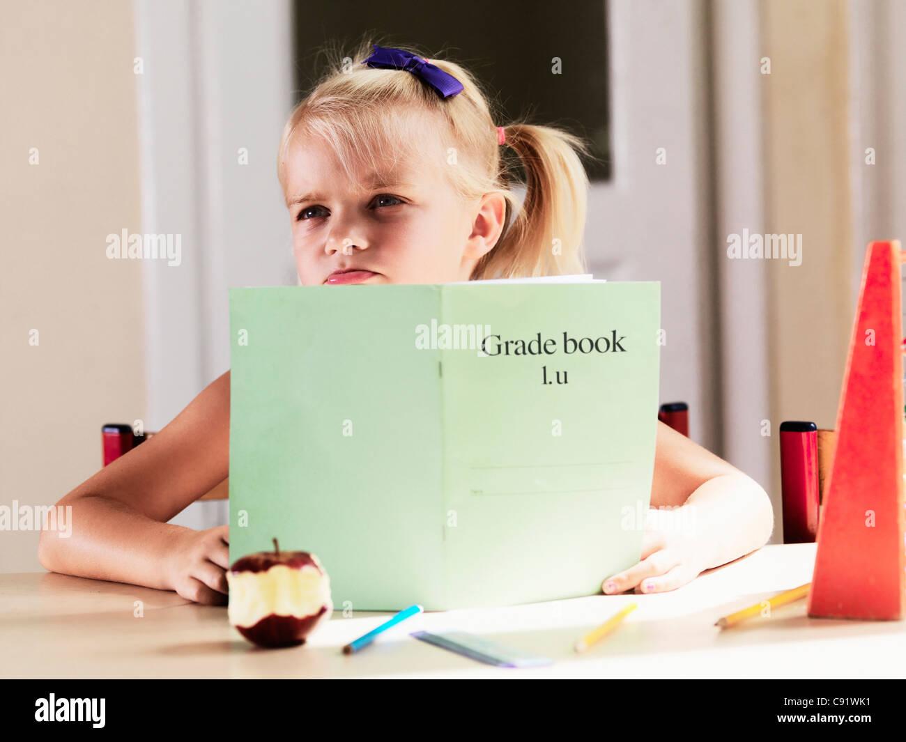 Bored girl doing homework at desk - Stock Image