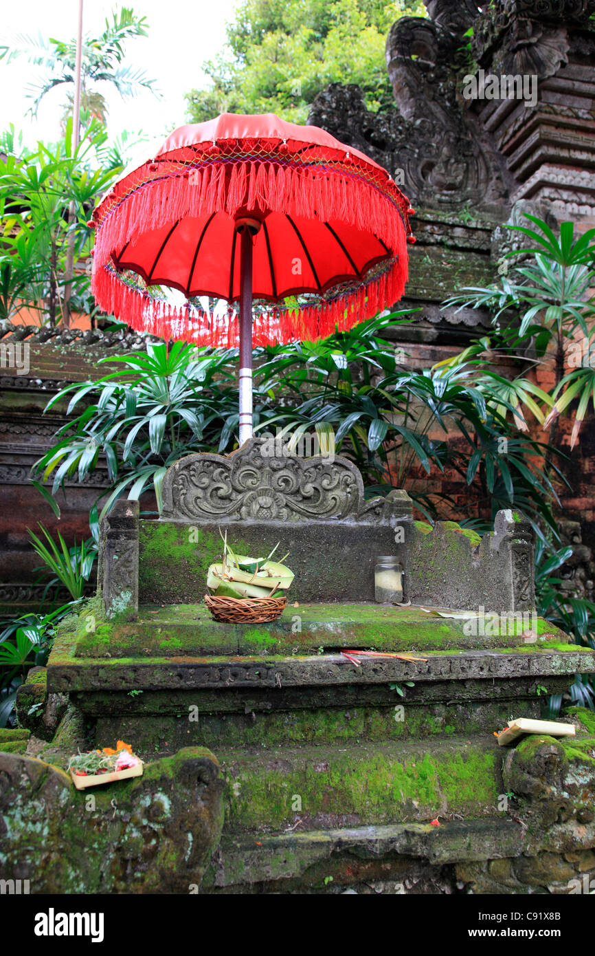 There are historic temples and shrines all over Bali island and the religious practice of making an offering by - Stock Image