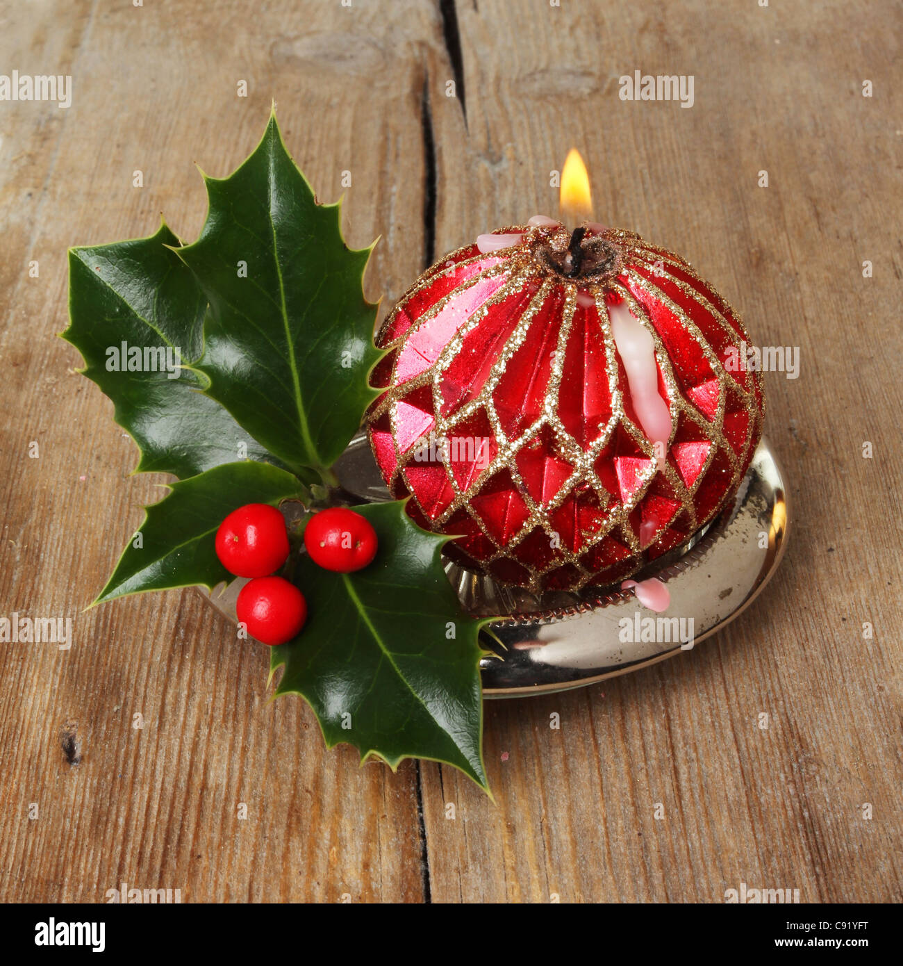 Decorative burning red and gold candle with a sprig of fresh holly on a background of old weathered wood - Stock Image