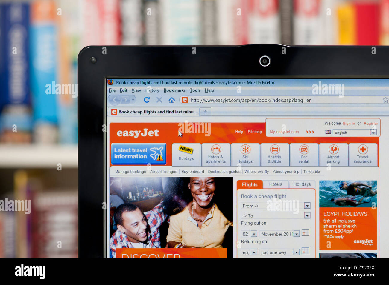 The easyJet website shot against a bookcase background (Editorial use only: print, TV, e-book and editorial - Stock Image