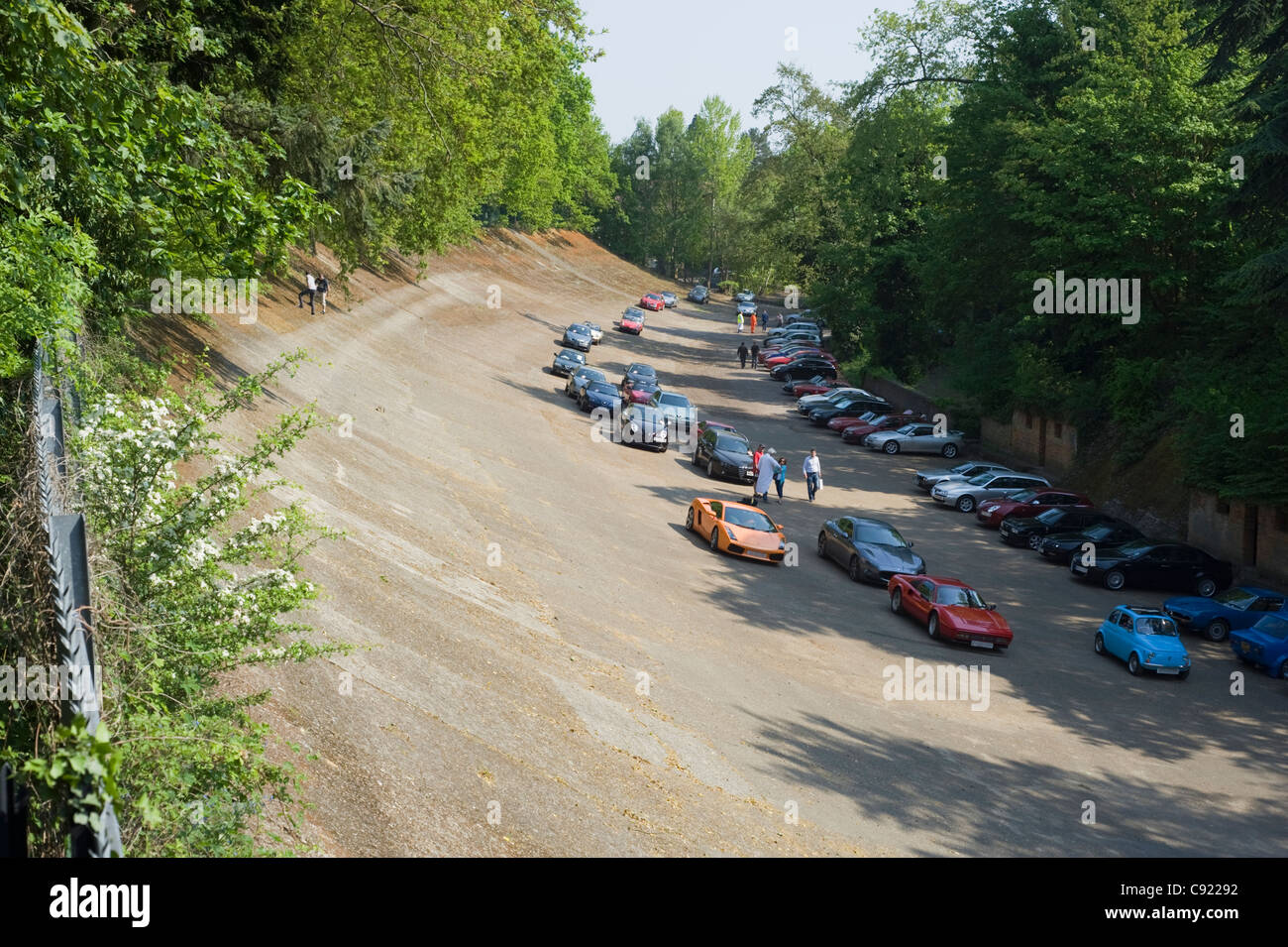 A Fiat 500 making it's way round the track past a line up of Italian cars at the Auto Italia Day at Brooklands - Stock Image