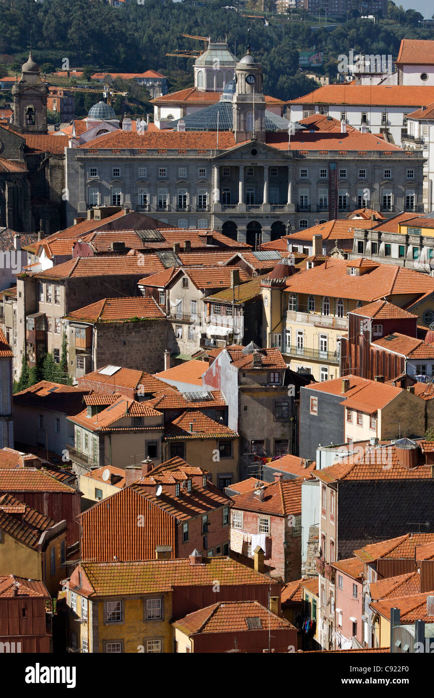 Red tiled roofs of Porto buildings with the facade of the Palacio Da Bolsa - Porto's Stock Exchange - in the - Stock Image
