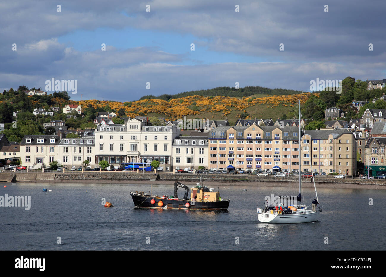 Houses along the harbour side and  boats moored at Oban which is a busy west coast port. - Stock Image
