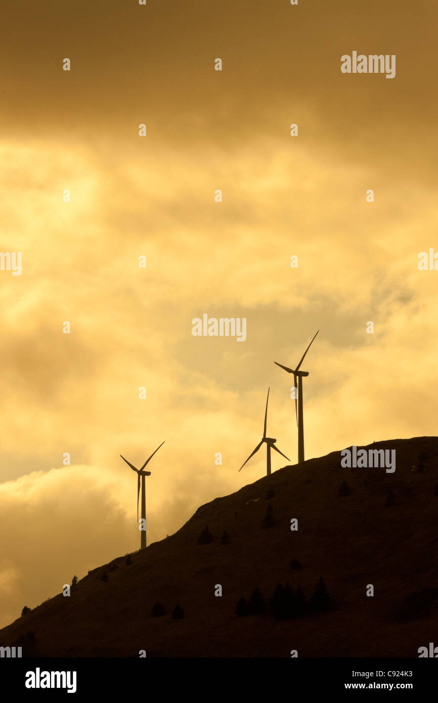 Silhouette view of wind generators on Pillar Mountain above Kodiak at sunset, Southwest Alaska, Spring - Stock Image