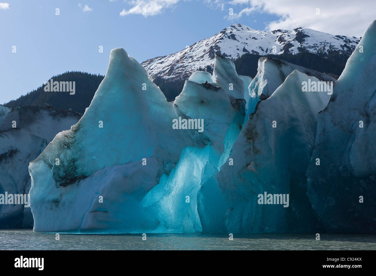 Sun shines through the face or terminus of Mendenhall Glacier on Mendenhall Lake in Alaska's Tongass Forest, - Stock Image