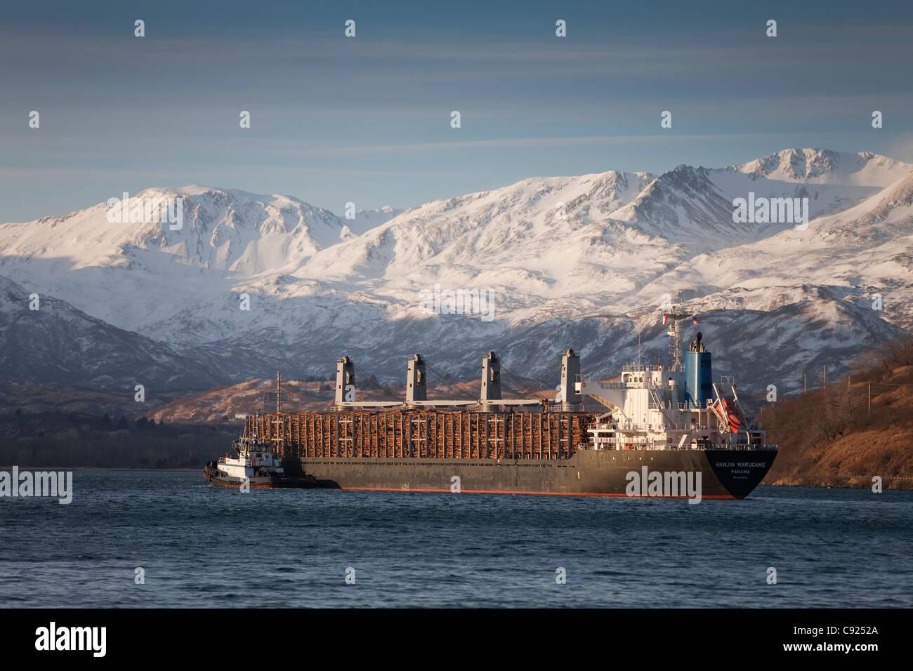 Panamanian ship Hanjin Marugame, assisted by a tug boat, departs Womens Bay, Kodiak Island, Southwest Alaska, Autumn - Stock Image
