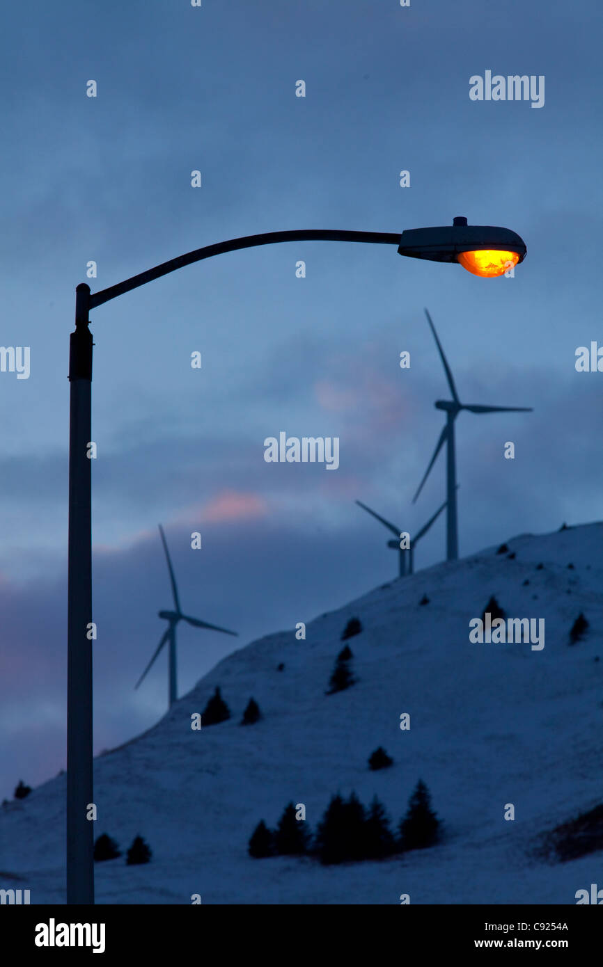 Lamp post glows warmly in late afternoon with wind turbines on top of Pillar Mountain behind City of Kodiak, Southwest - Stock Image