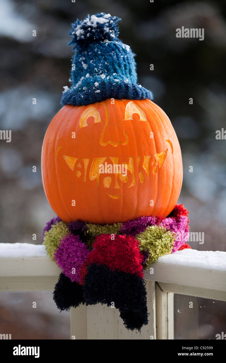Close up of a carved pumpkin with the word Alaska carved as teeth and sitting on deck railing , Alaska - Stock Image