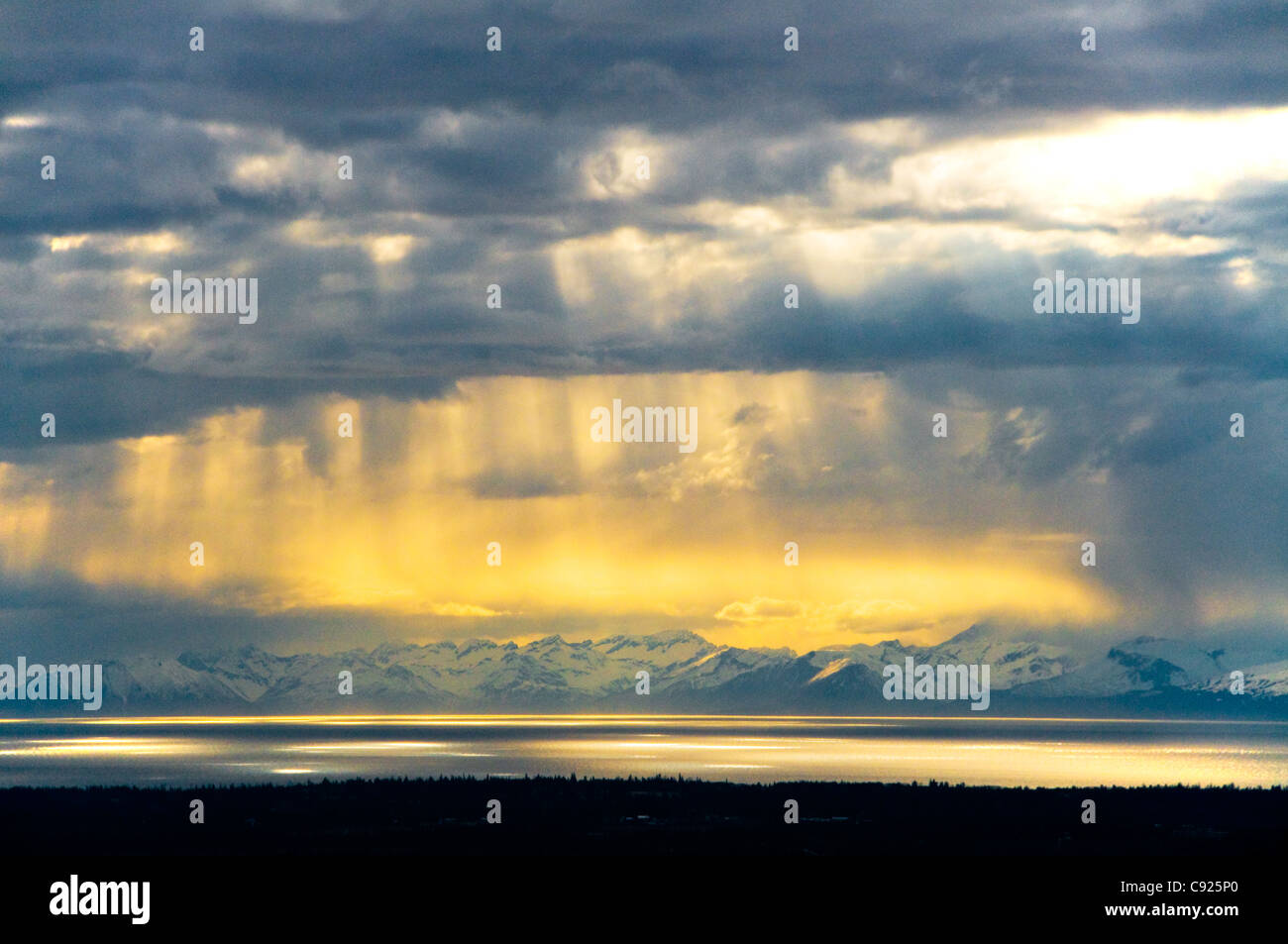 Sunrays peek through clouds over Cook Inlet with the Chigmit Mountains in the background, Kenai Peninsula, Alaska, - Stock Image
