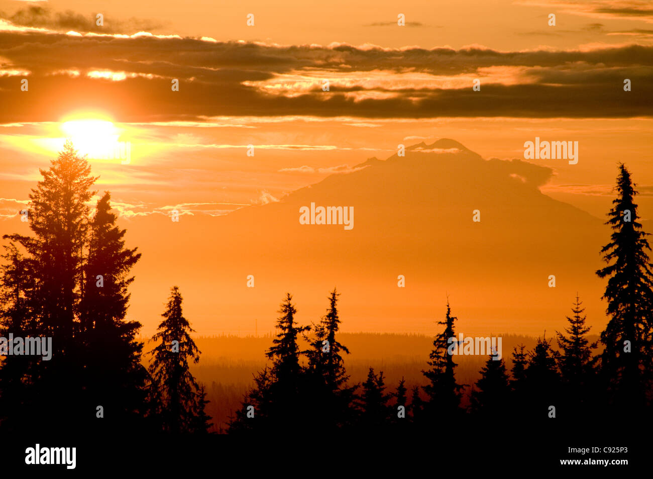 A setting sun silhouettes Redoubt Volcano across Cook Inlet as seen from the Kenai Peninsula in Southcentral Alaska, - Stock Image