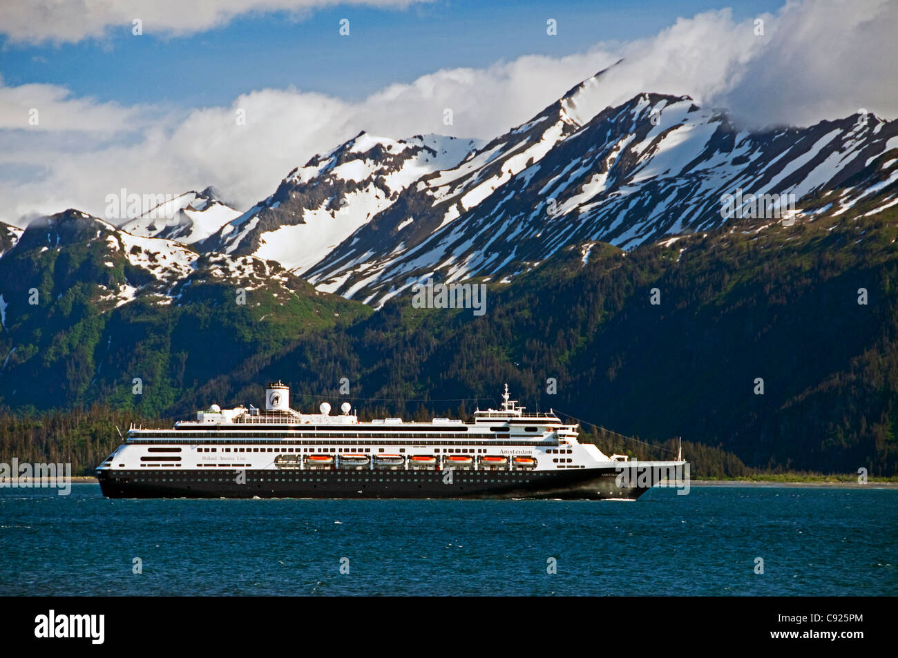 A cruise ship travels Kachemak Bay leaving port on the Homer Spit, Kenai Mountains in Kachemak Bay State Park, Alaska - Stock Image