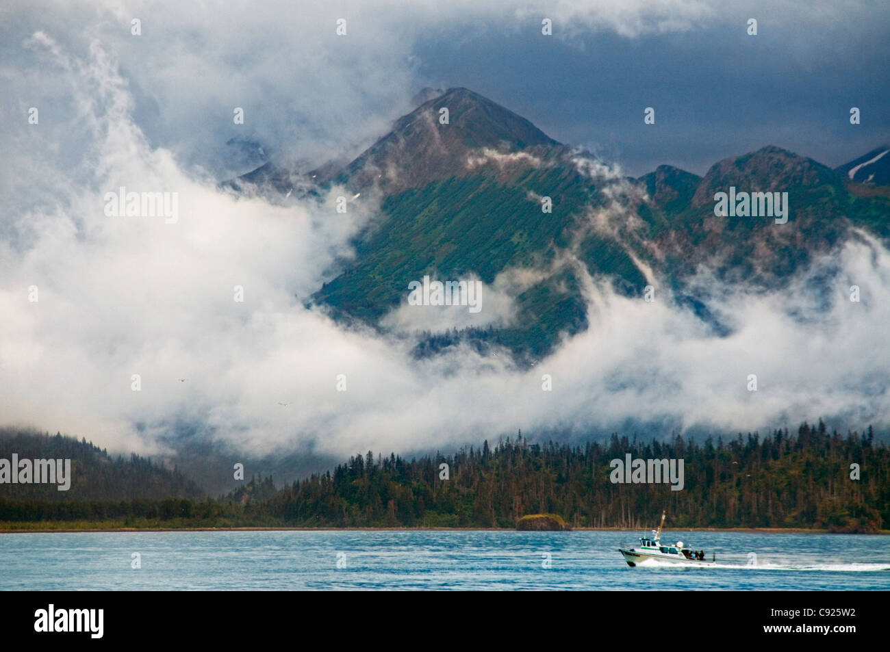 Sport fishing charter boat in Kachemak Bay with the fog enshrouded Kenai Mountains in the background, Alaska - Stock Image