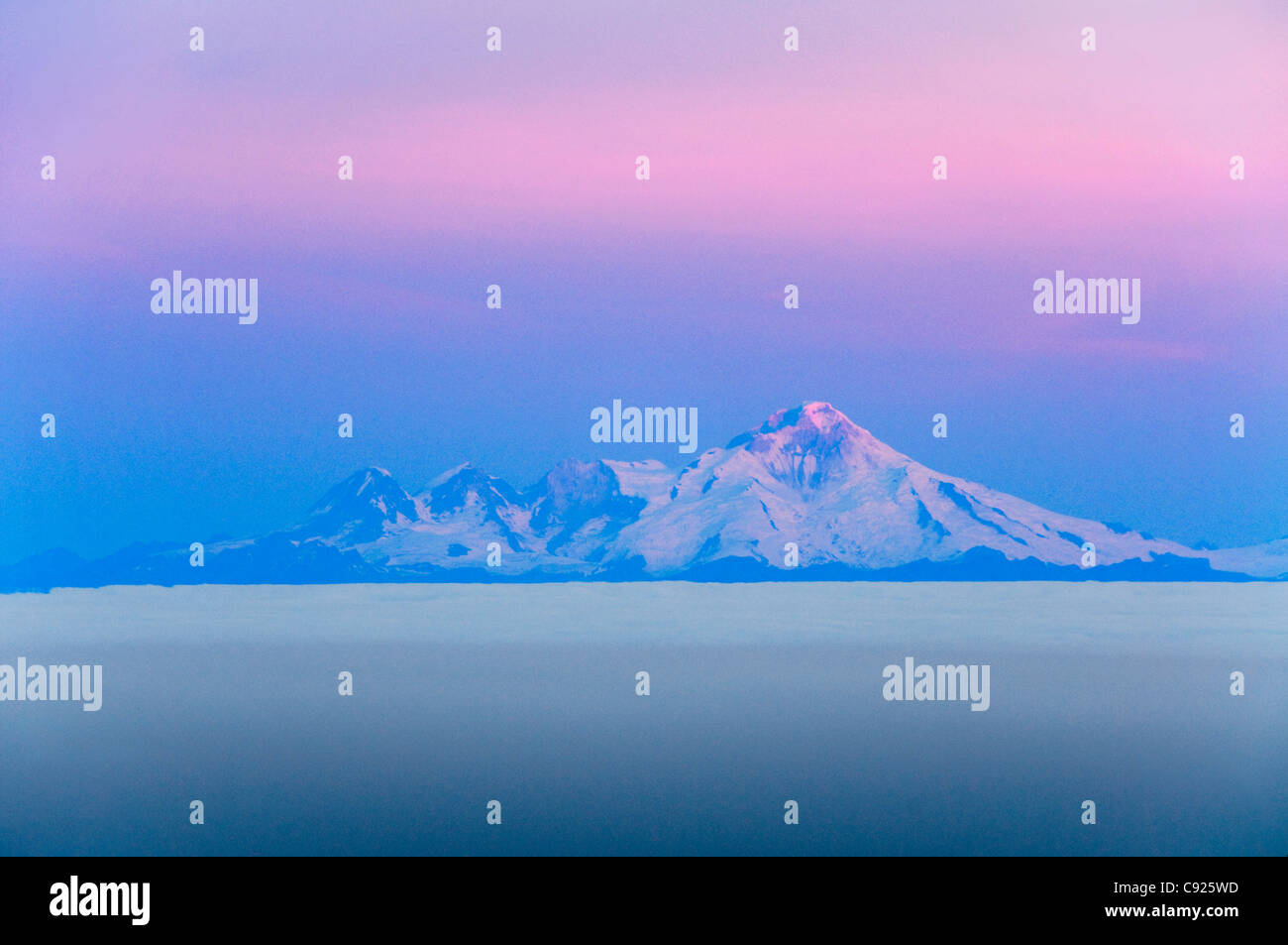 Daybreak on Mt. Iliamna and a low cloud layer as seen from Kenai Peninsula, Southcentral Alaska, Autumn - Stock Image