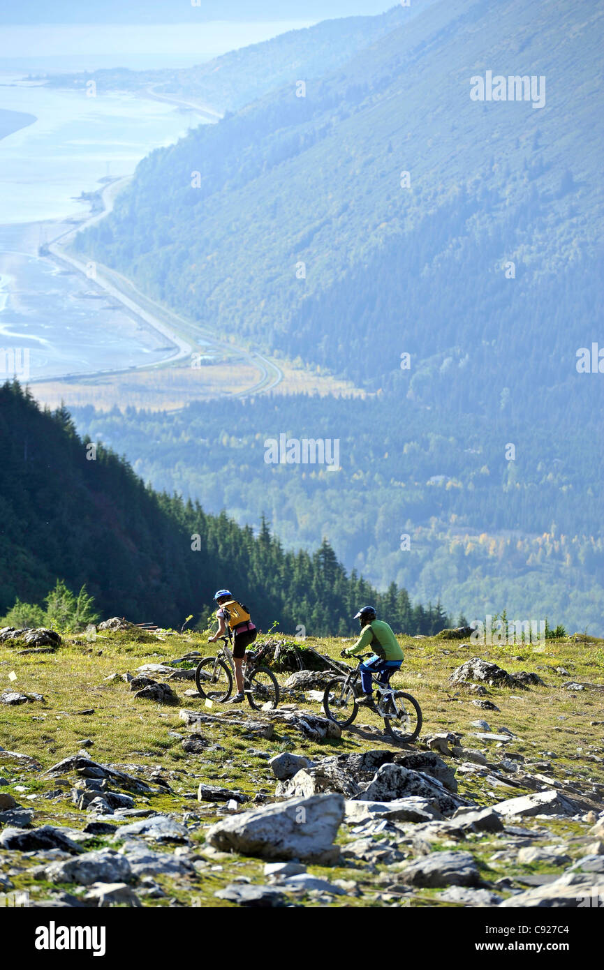 Two mountain bikers enjoy a day of tram serviced mountain biking at Alyeska Resort in Girdwood overlooking Turnagain - Stock Image