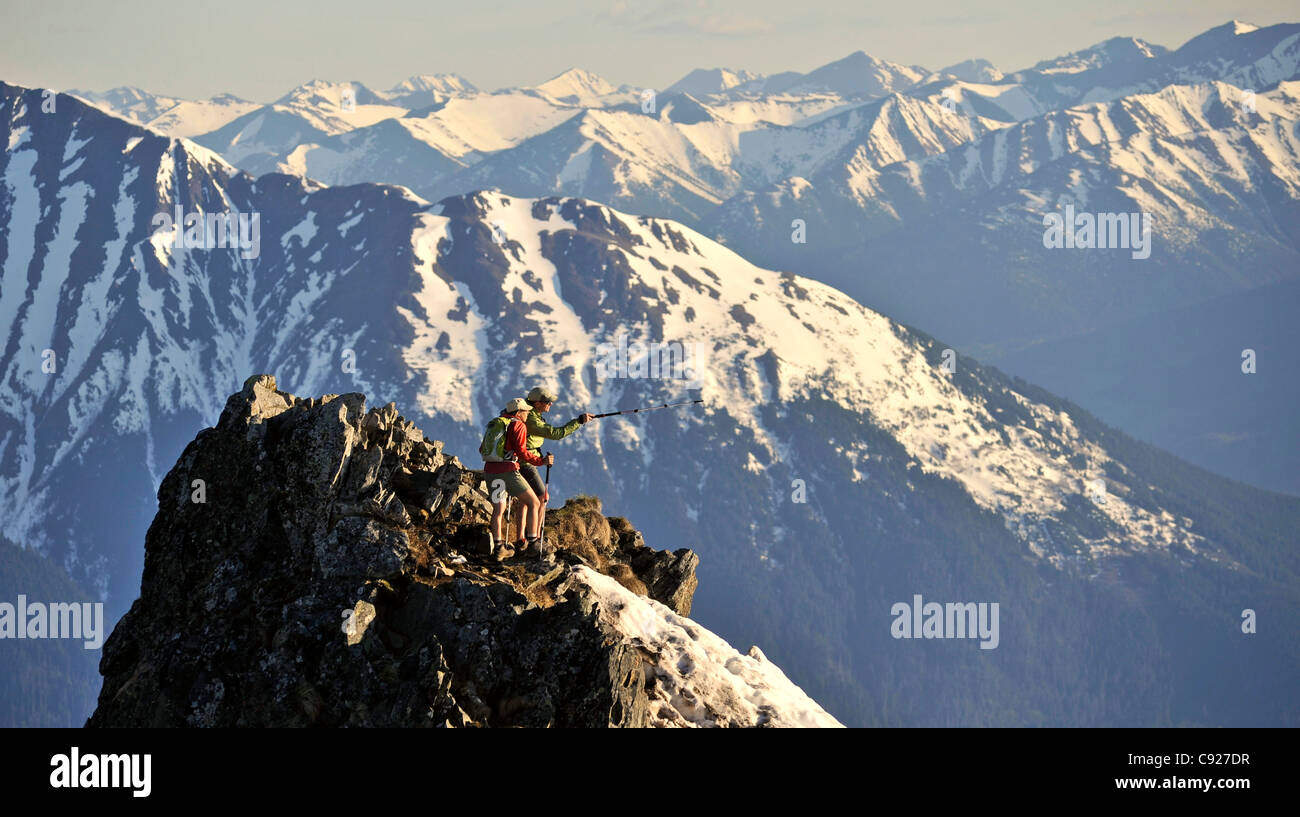 Couple stand on the summit of Bird Ridge in Chugach State Park with the scenic Chugach Mountains and in the background, - Stock Image