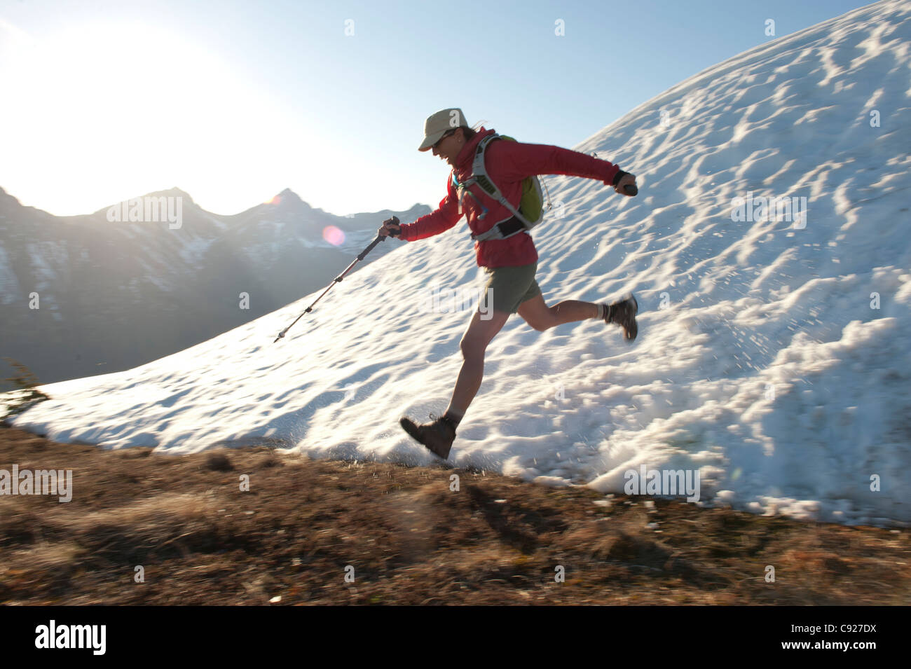 Female hiker hikes through snow while descending the Bird Ridge Trail above Turnagain Arm in Chugach State Park, - Stock Image