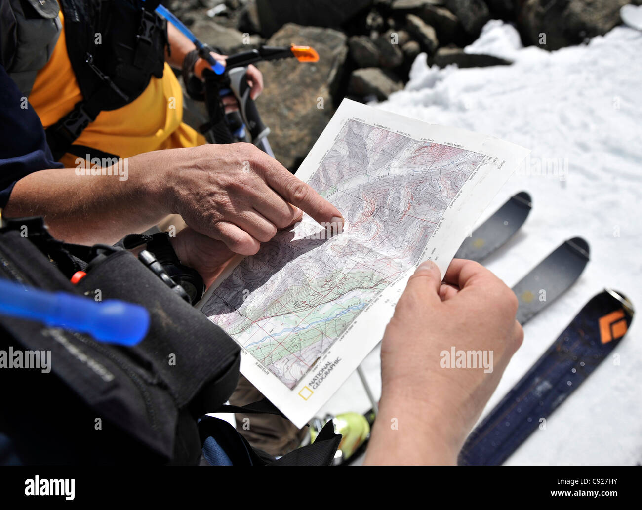 Two backcountry skiers review a map to navigate up Water Fall Creek valley, North Fork Eagle River, Alaska - Stock Image