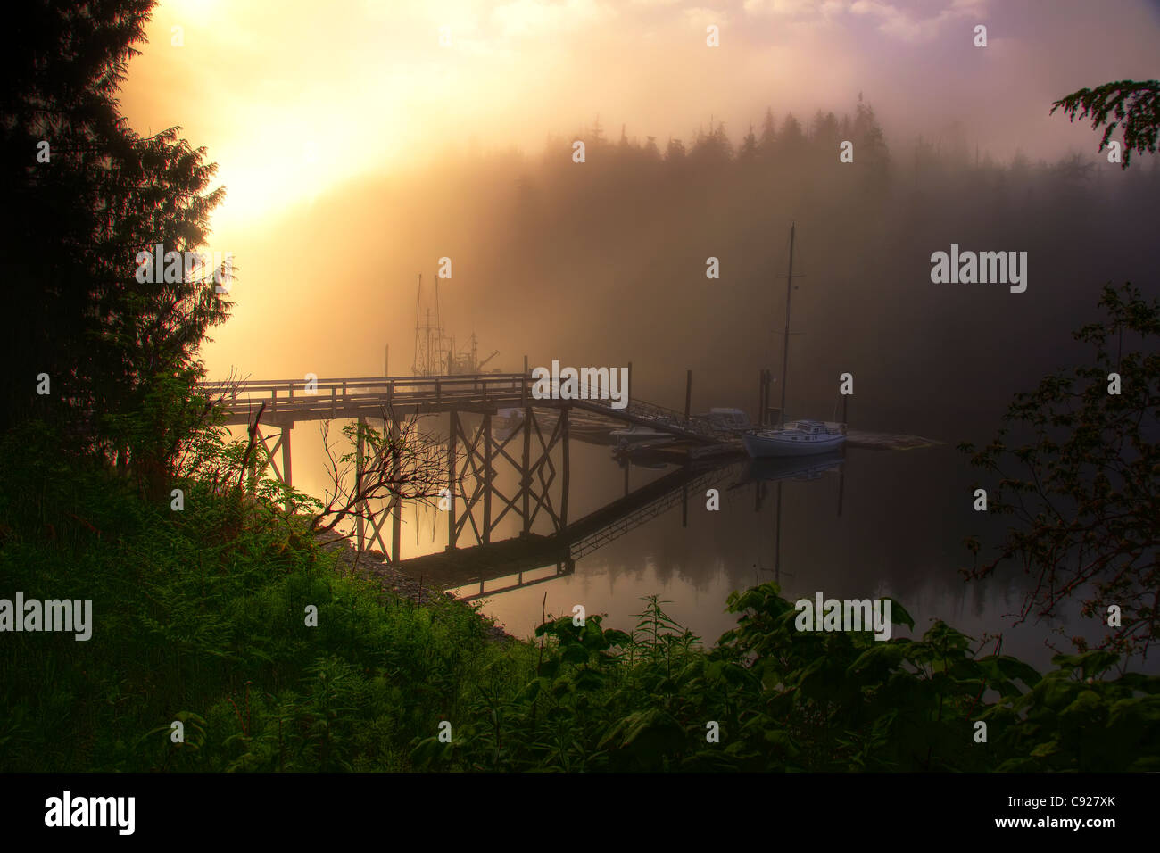 View of boat dock with sunrise through fog near Hollis, Prince of Wales Island, Tongass National Forest, Southceast - Stock Image