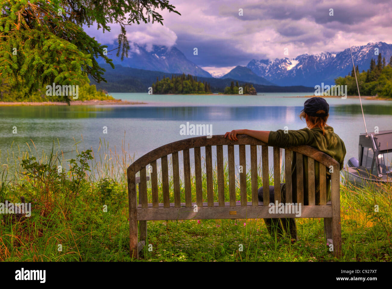 Woman enjoying the view of Lake Clark from an island bench, Lake Clark National Park, Southcentral Alaska, Summer, - Stock Image