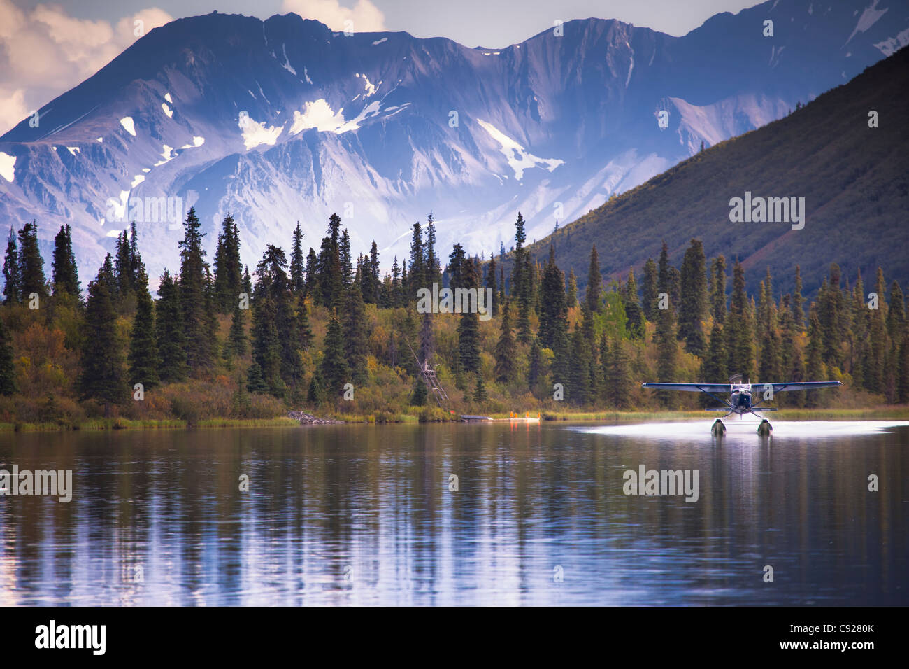 A Cessna 206 on floats lands on Puntilla Lake near Rainy Pass Lodge with mountains and fall colors in the background, - Stock Image