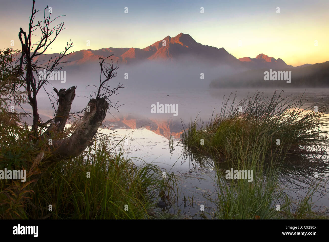 Sunrise on Pioneer Peak with small, misty lake in the foreground, Mat-Su Valley, Southcentral Alaska, Autumn - Stock Image