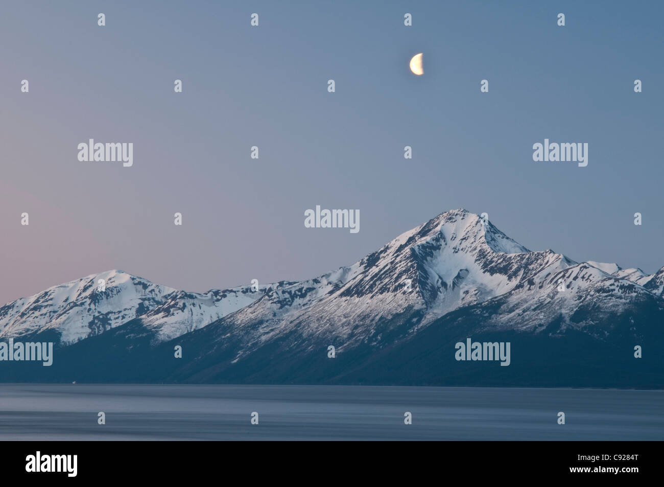 A half moon over the Kenai Mountains and the Turnagain Arm at dawn, Southcentral Alaska, Spring - Stock Image