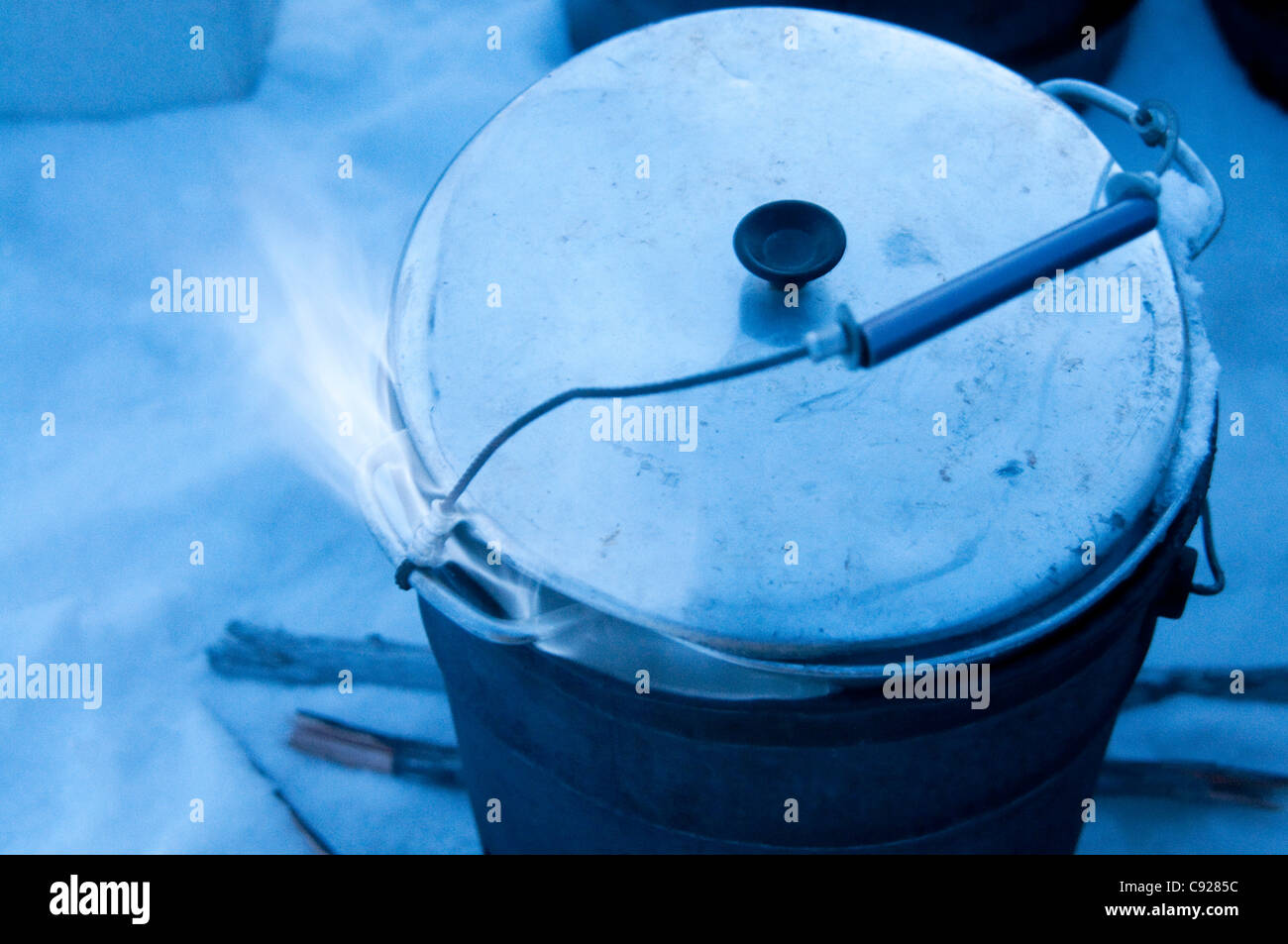Mehtanol-fueled flame heats up a pan of snow to melt water for a dog team, Gates of the Arctic National Park & - Stock Image