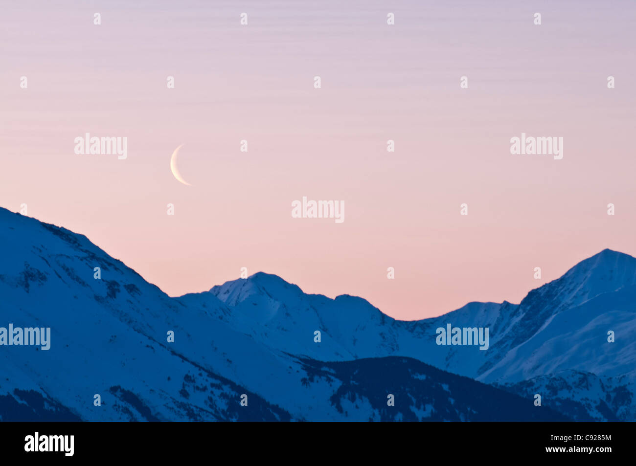 Cresent moon rises at dawn over the Kenai Mounatins along the Turnagain Arm, Southcentral Alaska, Spring - Stock Image