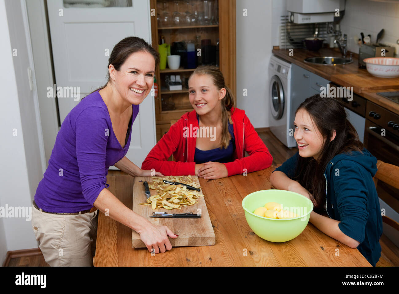 Mother and daughters cooking in kitchen - Stock Image