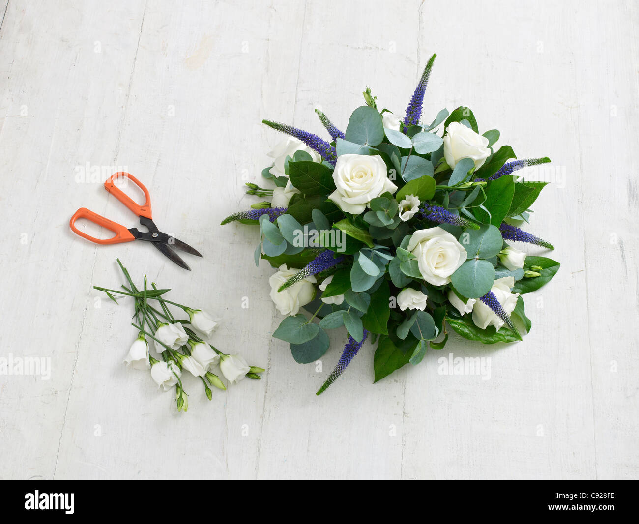 Floral foam arrangement, white lisianthus, white roses, purple veronica, salal and eucalyptus foliage - Stock Image