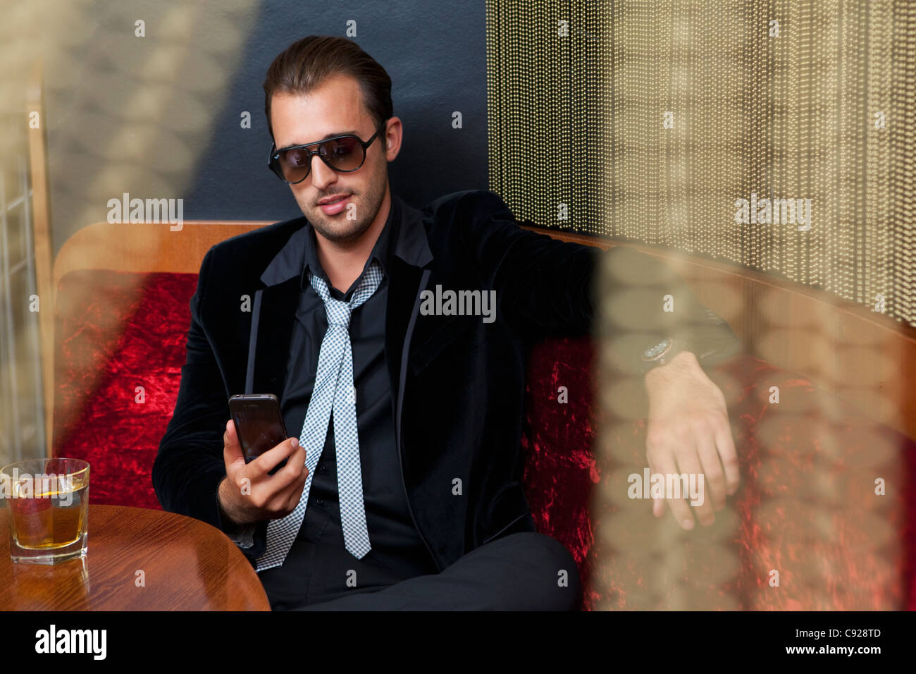 Man using cell phone in bar - Stock Image