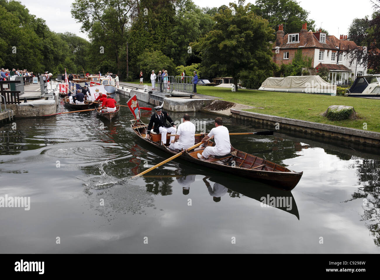 Swan Uppers in their traditional uniforms row skiffs down the river during Swan Upping, River Thames, Henley, England - Stock Image