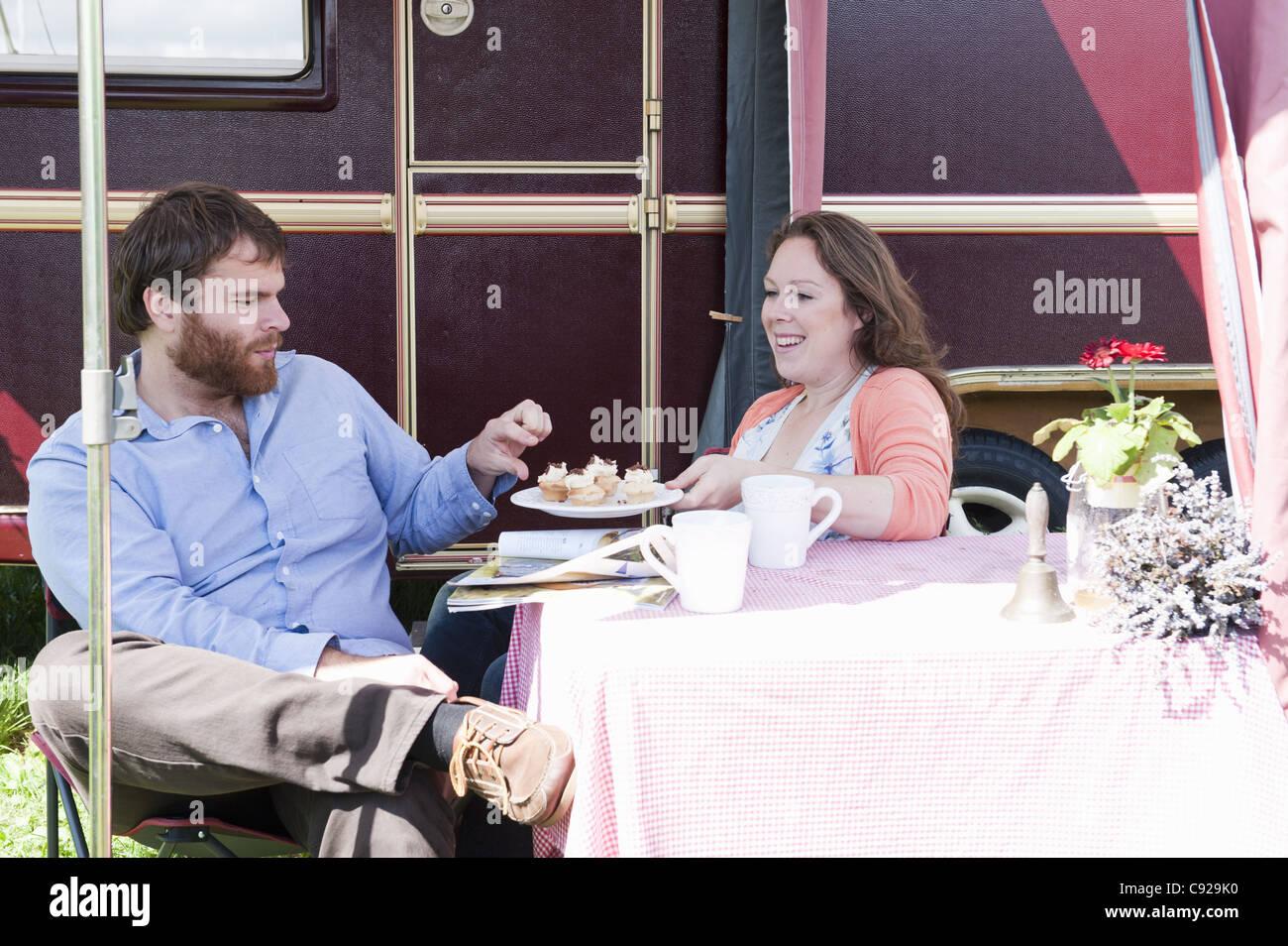Couple picnicking outside trailer - Stock Image