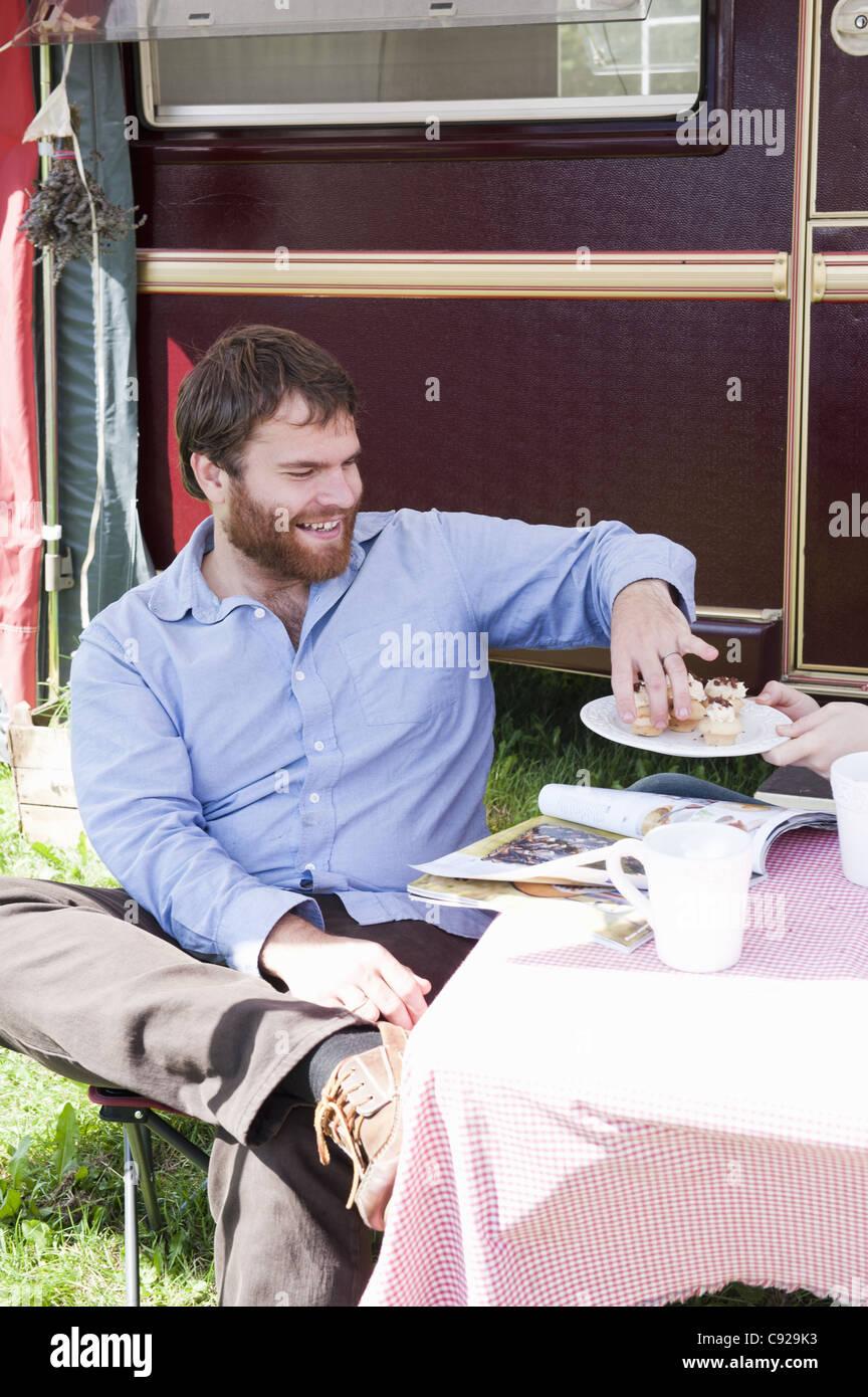 Man picnicking outside trailer - Stock Image