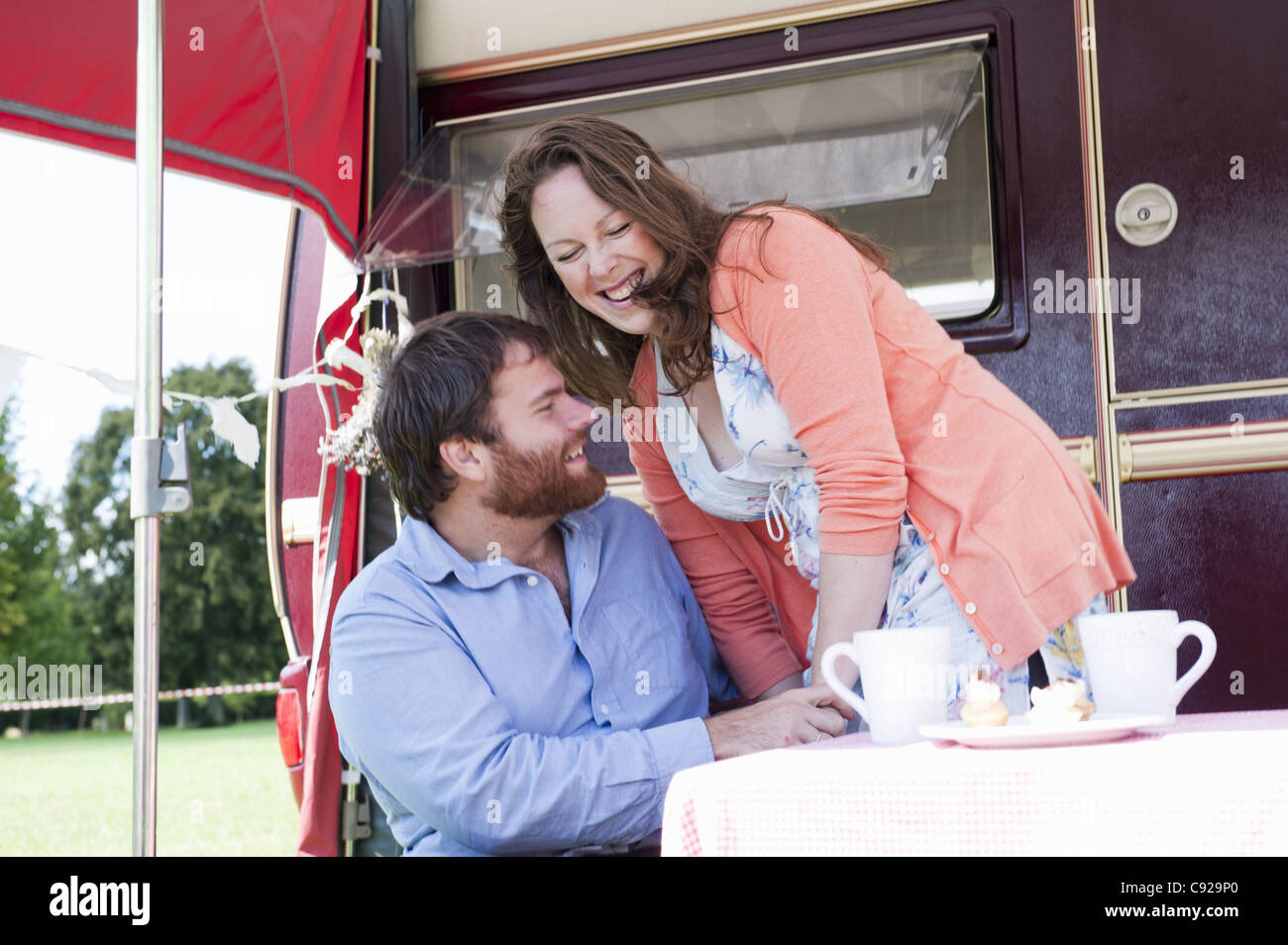 Couple picnicking outside trailer - Stock Image