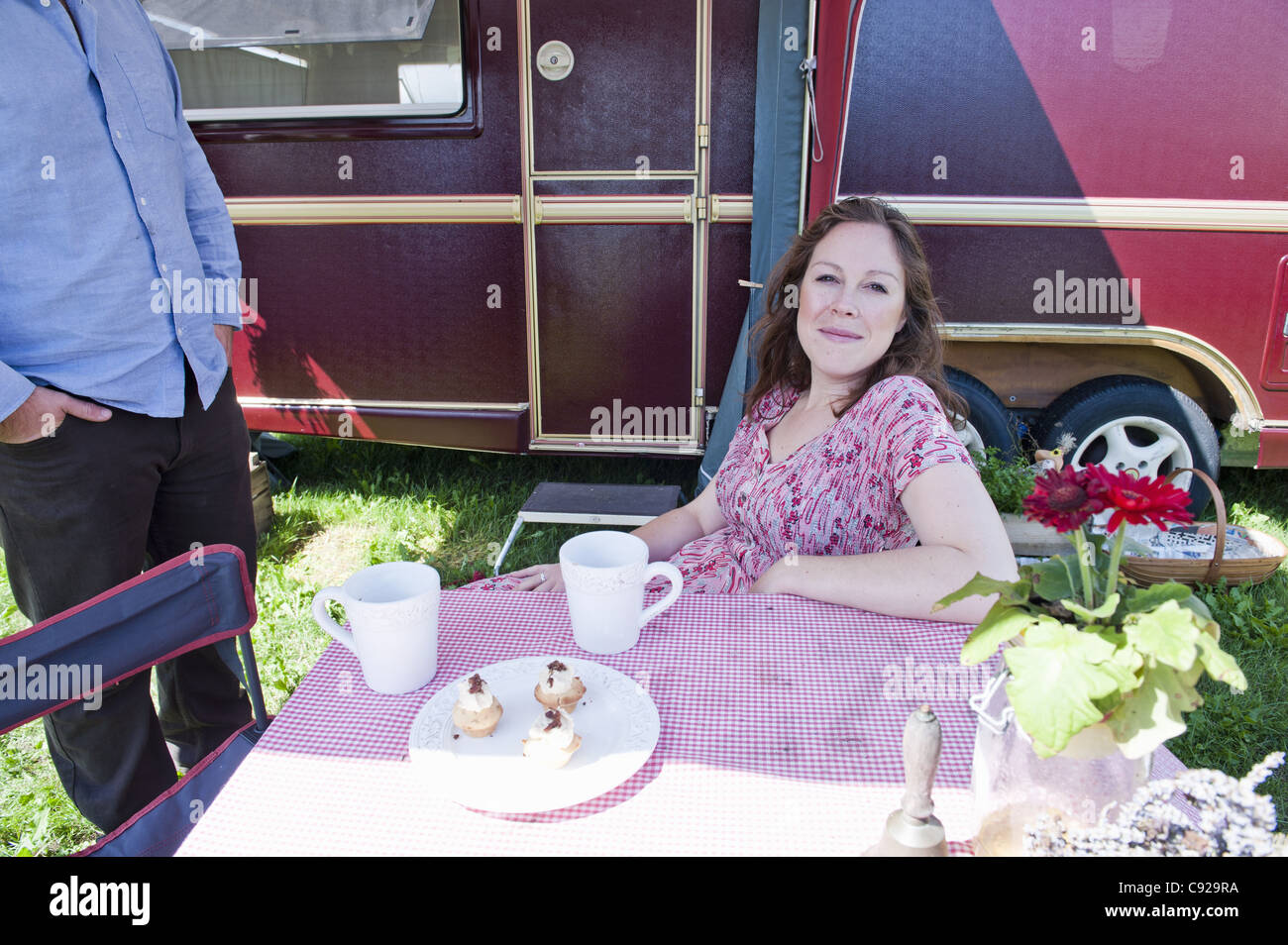 Woman picnicking outside trailer - Stock Image