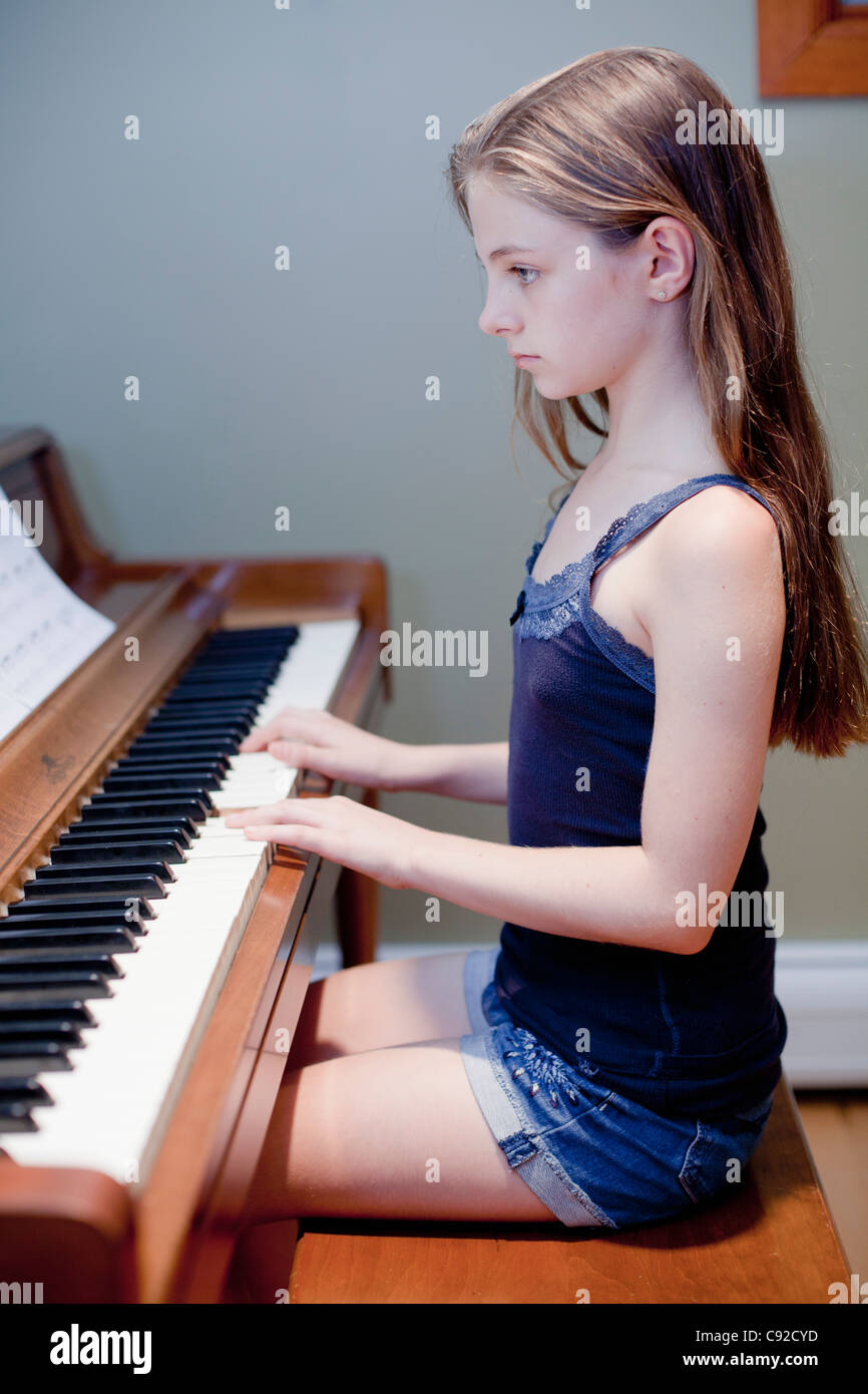 Girl practicing piano indoors - Stock Image
